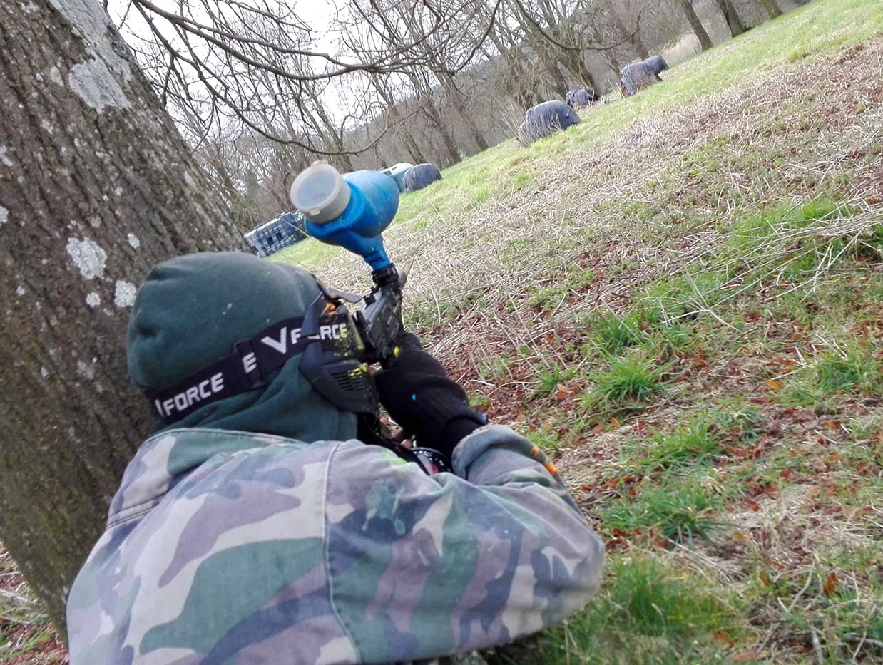 Paintball player hiding behind a tree whilst firing his gun across an open field.