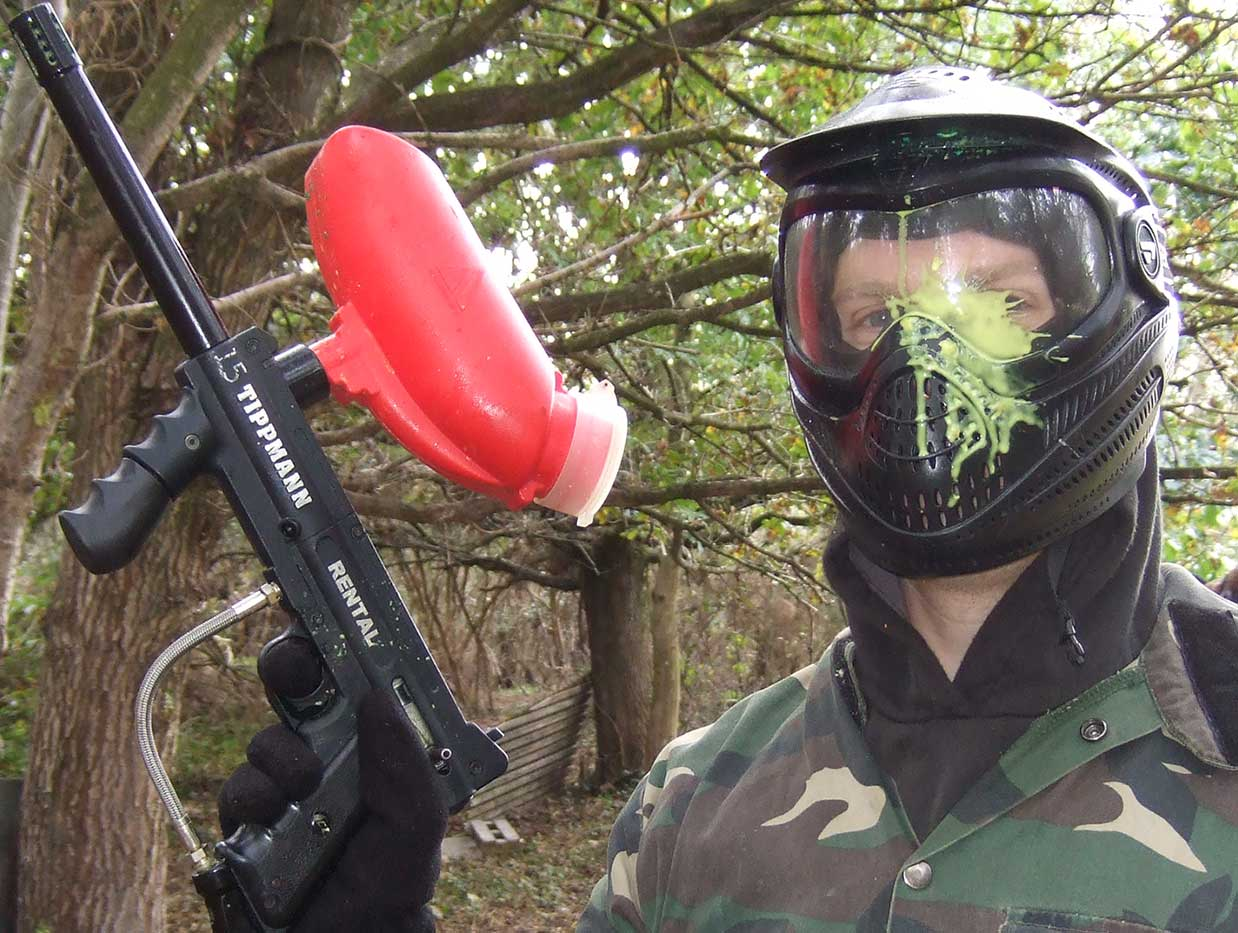 Man with yellow splat to his mask holding up his paintball marker in the woods.