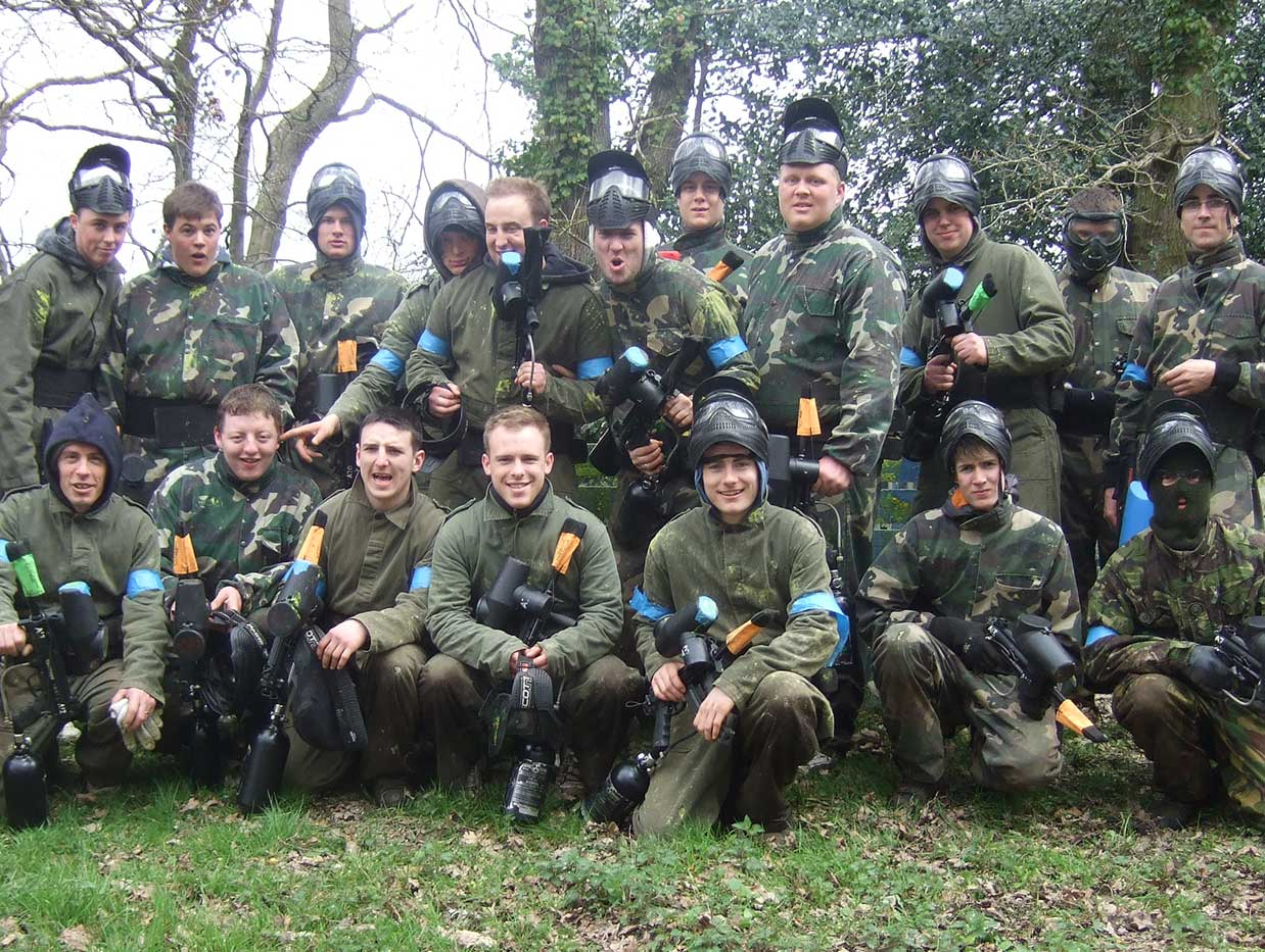 Team photo of paintball players dressed in camouflage overalls posing with paintball guns.