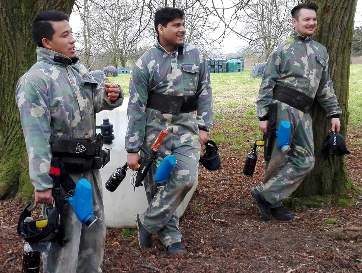Three paintballers holding guns having a break whilst chatting after playing a game of capture the flag.