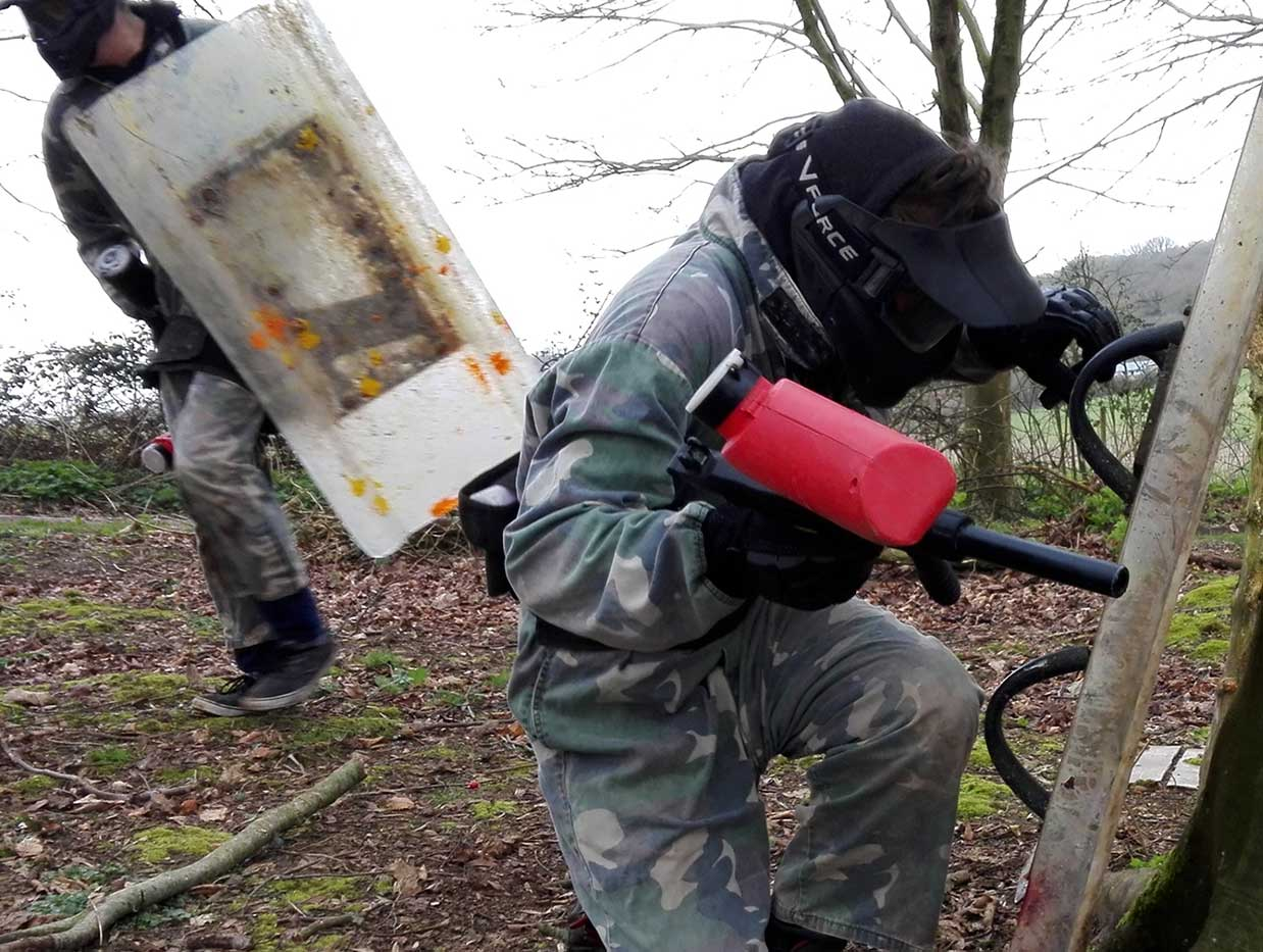 Two men from the red team repel an attack whilst holding riot shields for protection.
