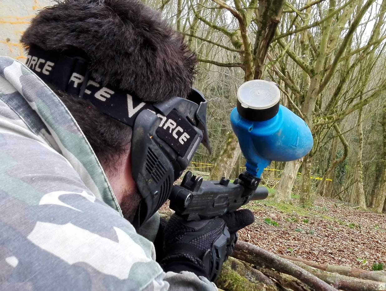 A member of the blue team aims over cover to shoot an opposing player with his paintball gun.