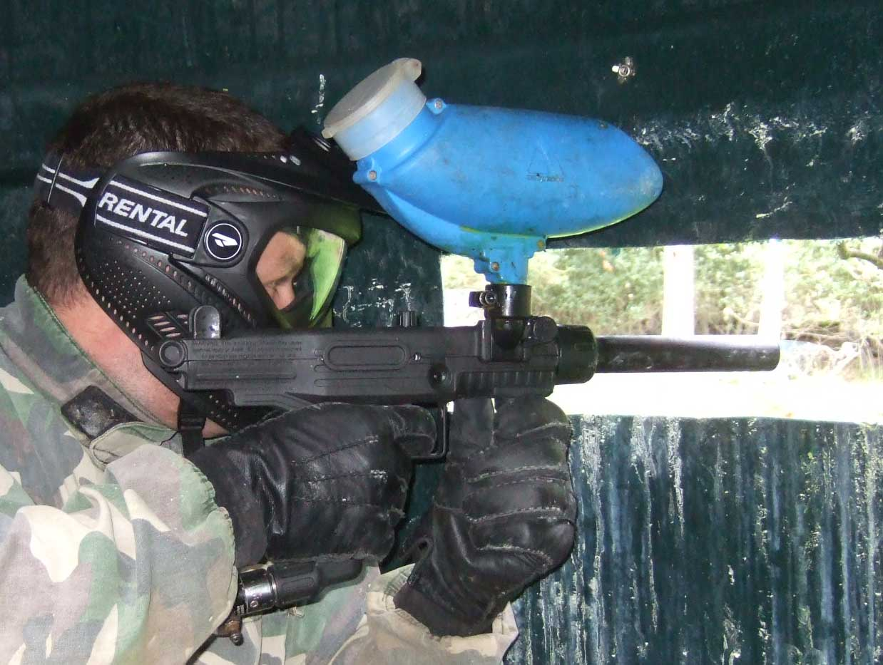 Close up of a man firing his paintball marker out of a pill box bunker during a game.