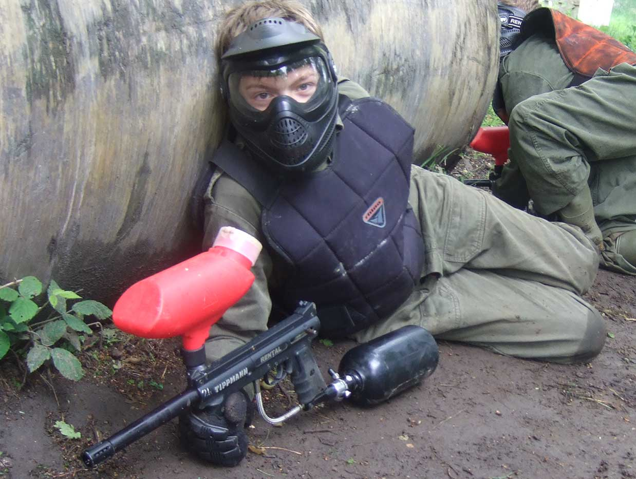 Child wearing a mask and body protection hiding behind a tube during a paintball fight.