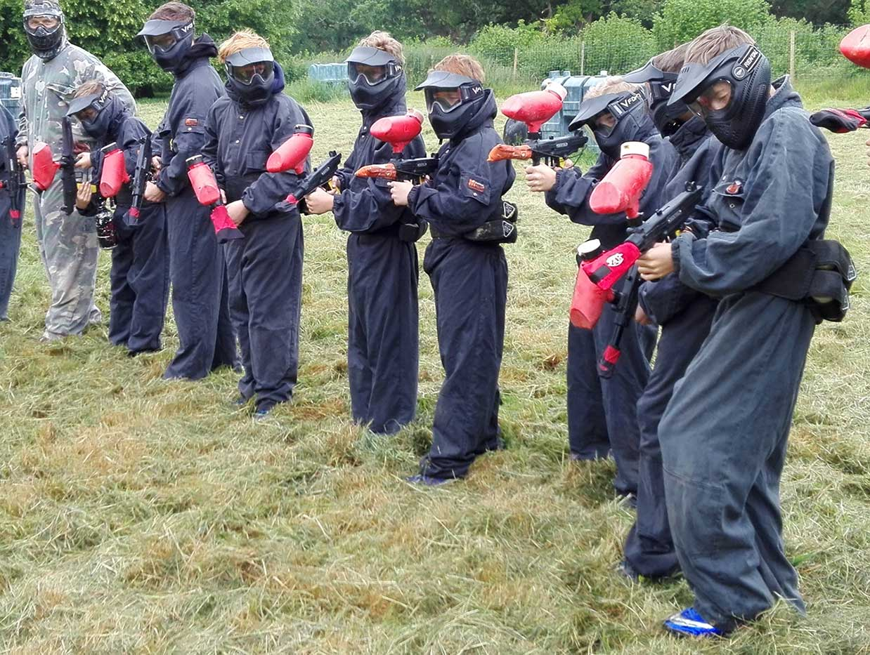 Red team standing in grass field preparing their paintball markers before a game.