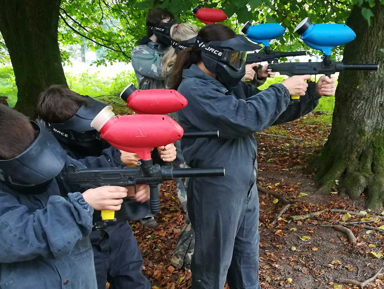 Youth members of the blue and red team test firing their paintball guns from under trees.