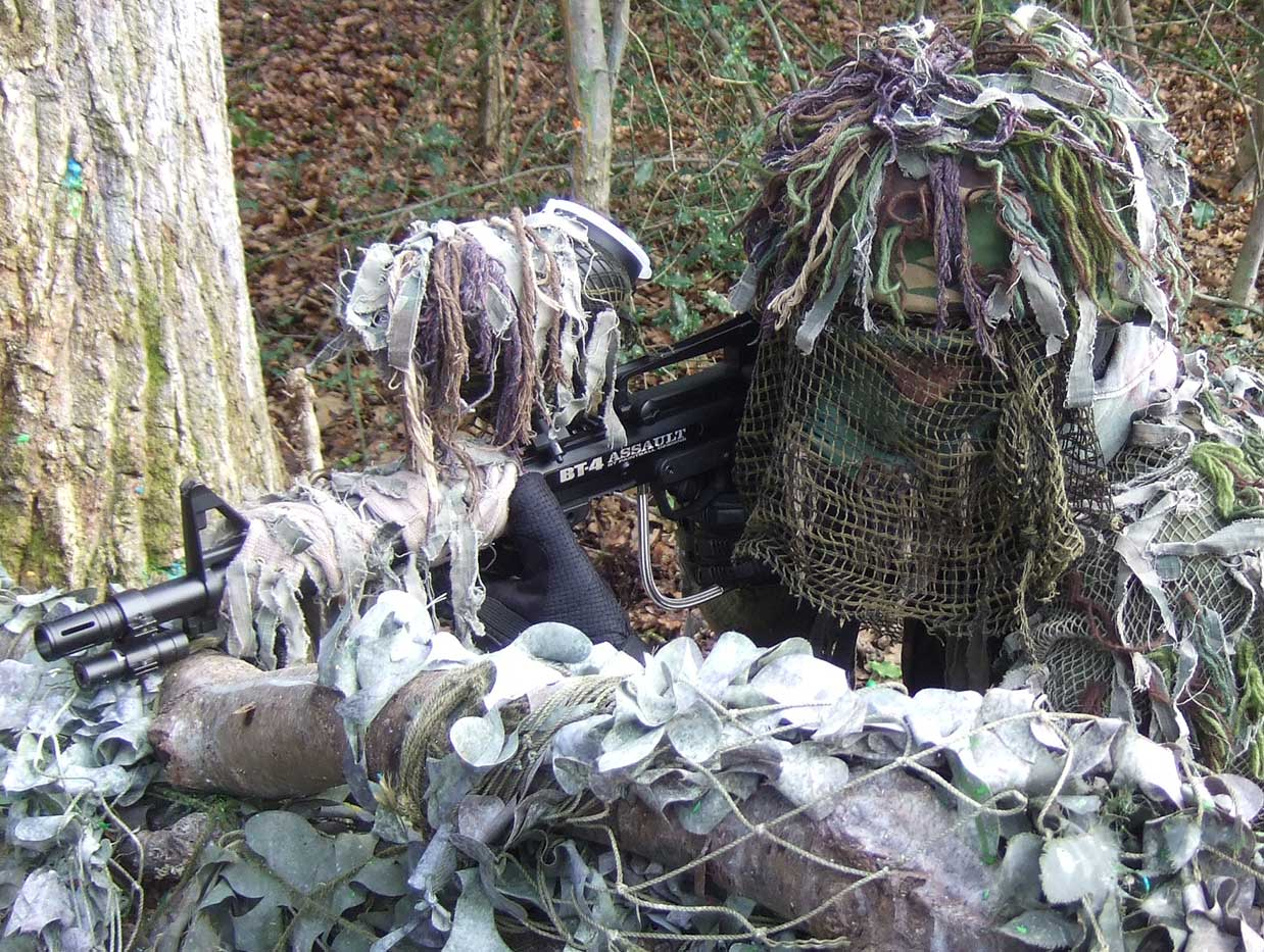 Paintball sniper dressed in a ghillie suit takes aim over a log barricade.