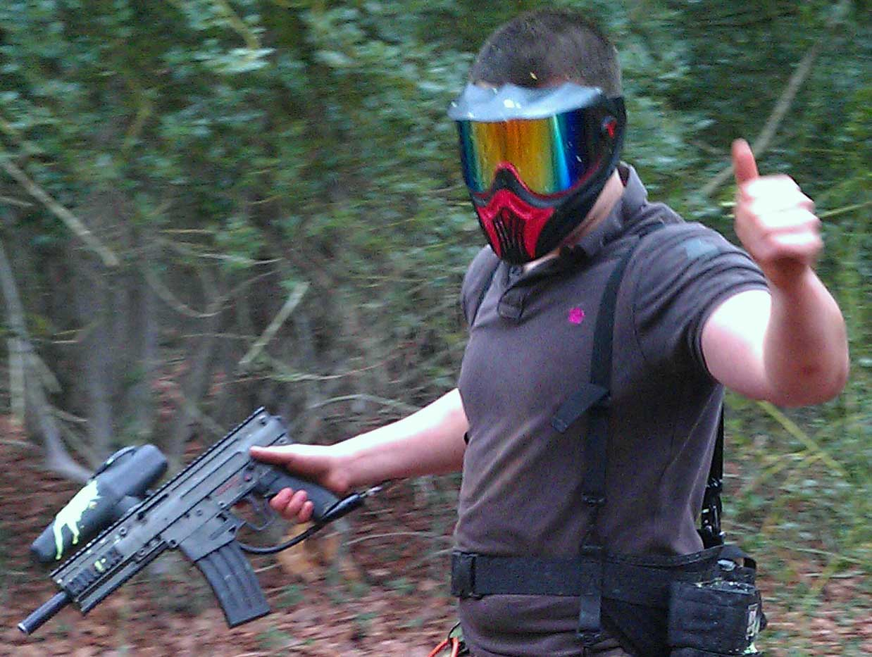 Man with paintball gun covered in splats gives the thumps up as he walks into combat.