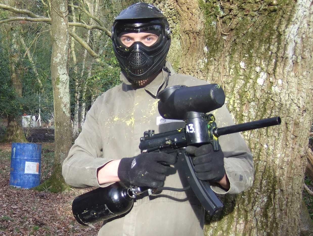 Player in green coveralls and mask stands next to tree with a rapid firing paintball gun at the ready.