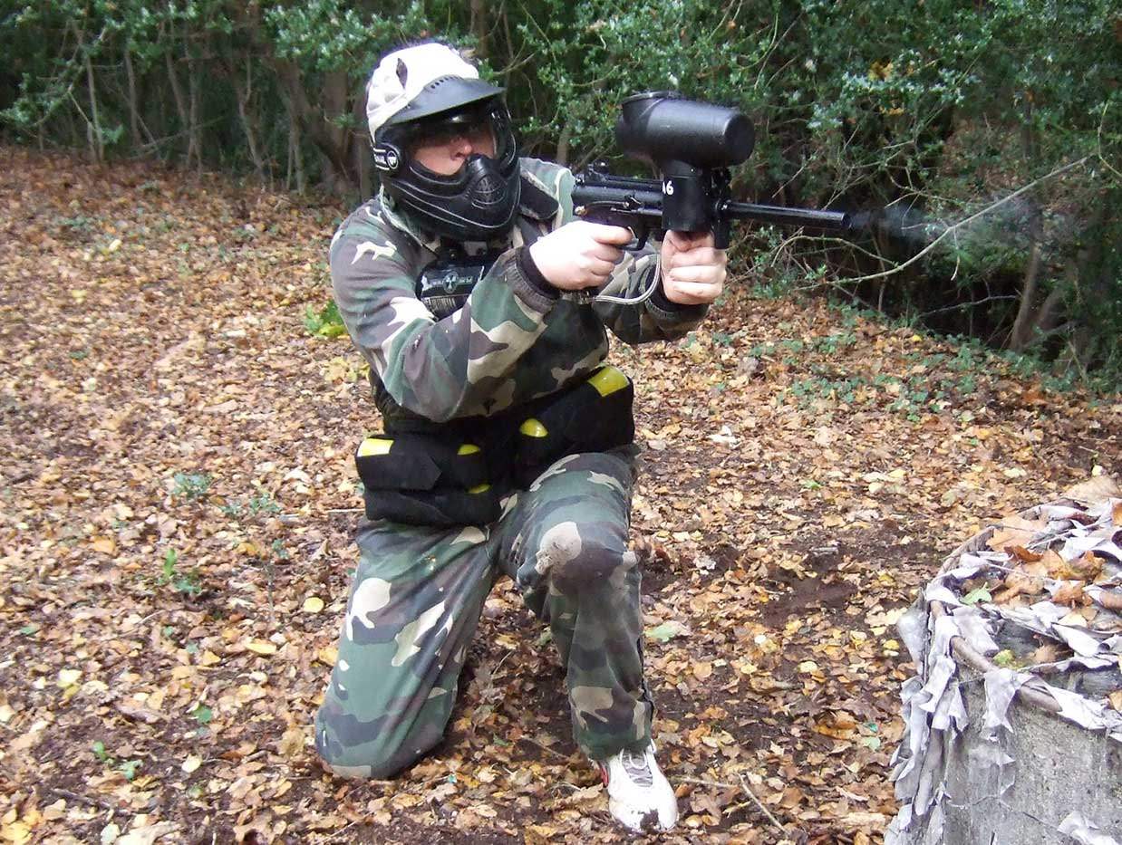 Man lays down covering fire for his team mate using his tippmann paintball gun.
