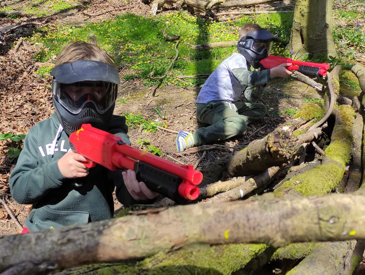 2 children firing .50 calibre paintballs over a wood barricade