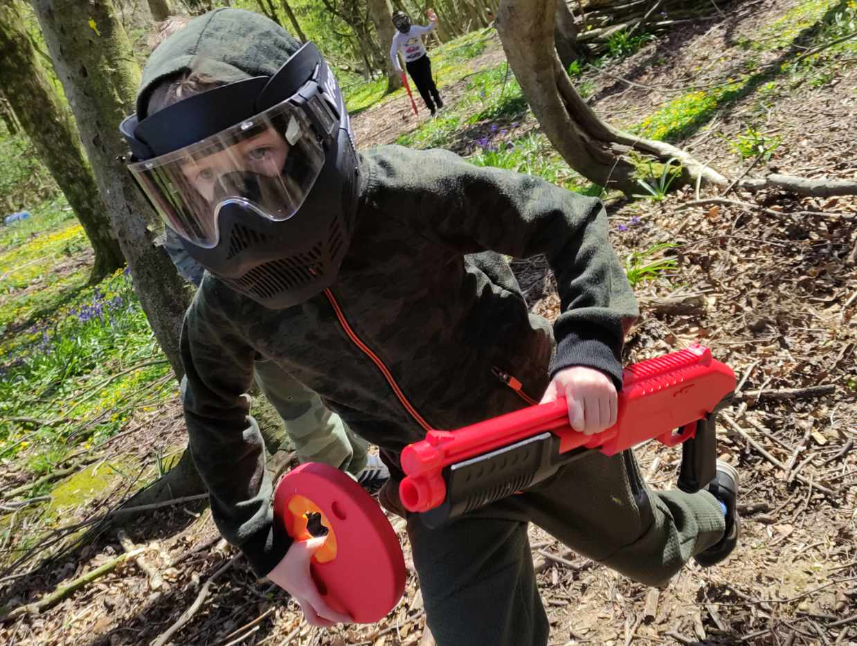 child running with a z200 splatmaster shotgun during a youth paintball session